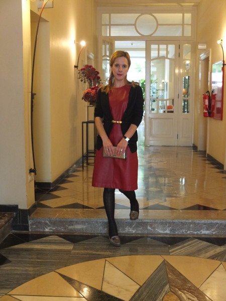 At the entrance of the fine boutique hotel T'Sand wearing a Boss leather shift dress, cashmere cardigan by Allude, vintage belt and Sergio Rossi shoes